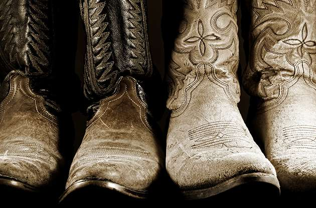 Two pairs of well worn cowboy boots in high contrast light.