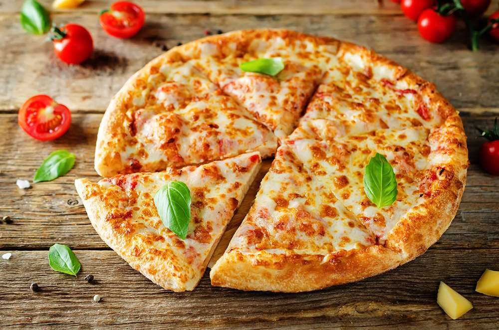 Pizza with cheese, tomato sauce and fresh tomatoes on a wood background. toning. selective focus