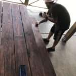 white-buffalo-saloon-man-applying-stain-to-wooden-picnic-table